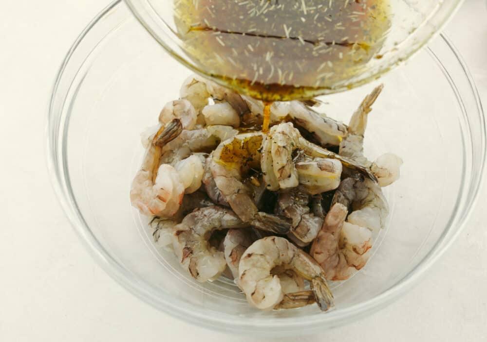 Pouring marinade over raw shrimp.