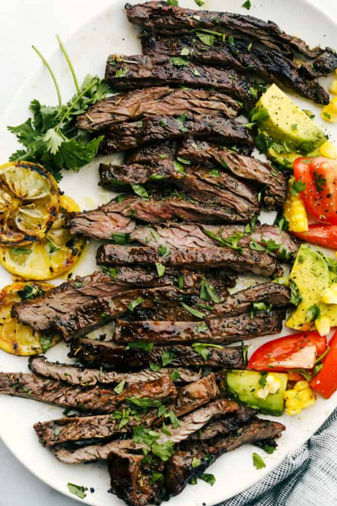Sliced grilled skirt steak on a plate with garnishes.