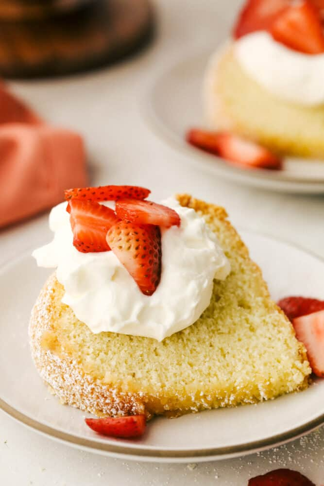 A piece of sour cream pound cake with whipped cream and strawberries.