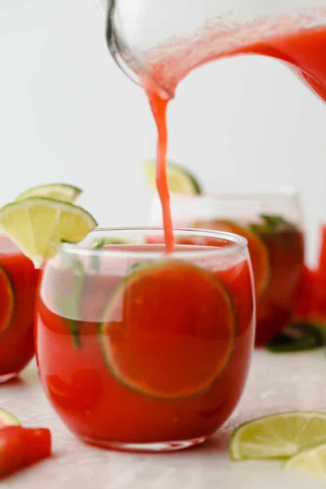 Pouring watermelon agua fresca into glass