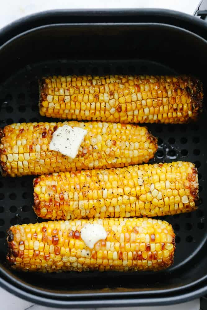 Air Fryer corn on the cob in the basket with butter.