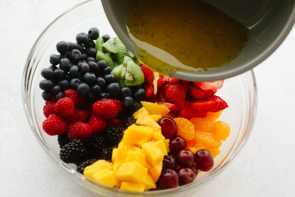Pouring lime dressing over fruits.