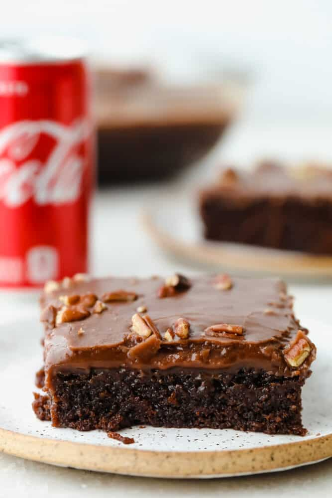 A slice of Coca-Cola cake topped with nuts.