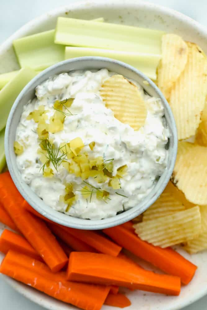 Dill pickle dip on serving dish with chips and veggies.