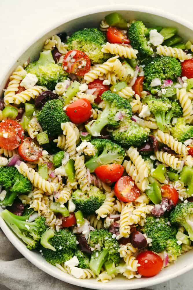 Greek broccoli pasta salad in a white bowl.