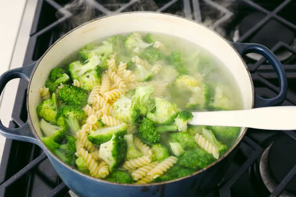 Boiling broccoli and pasta in a pot.