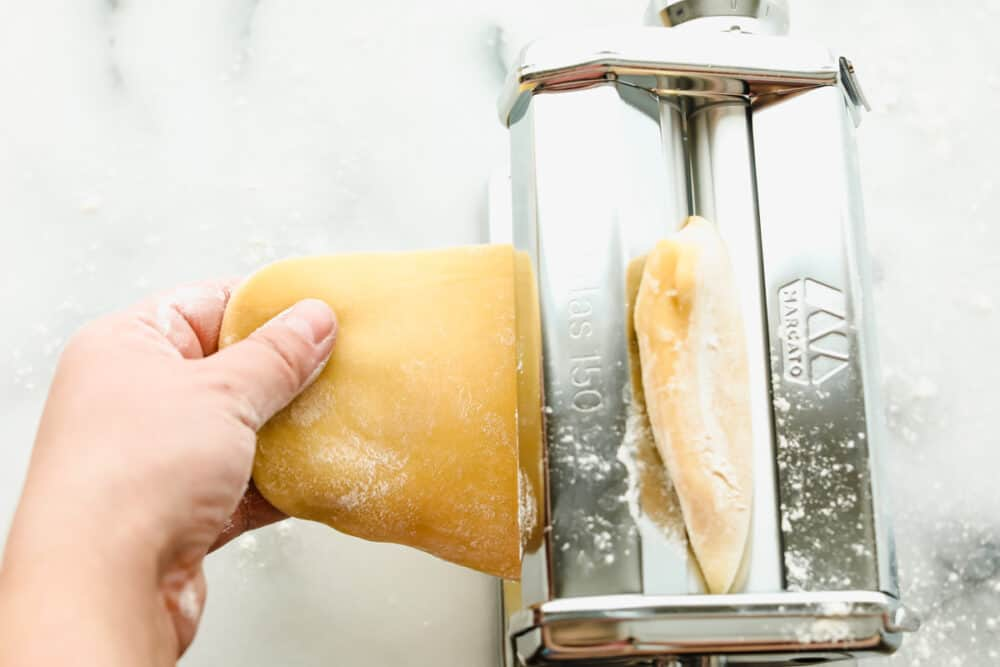 Feeding the dough into a pasta roller.