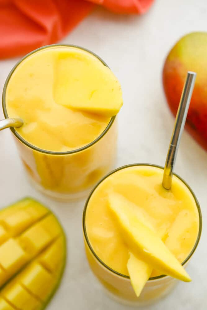 Top of view of a thick creamy smoothie garnished with fresh mango.