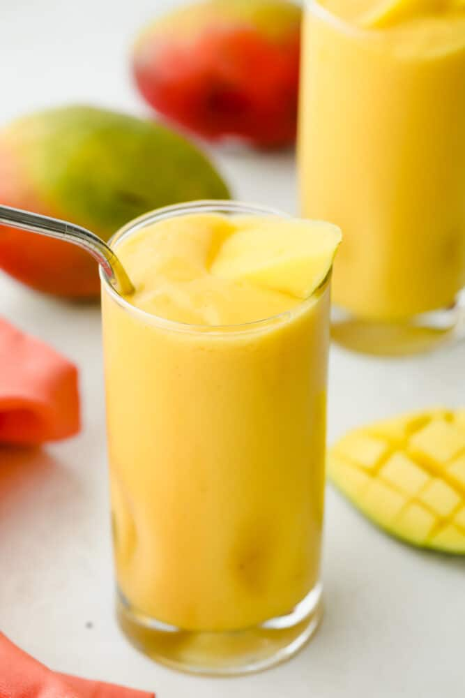 Mango smoothie in a glass with a straw.