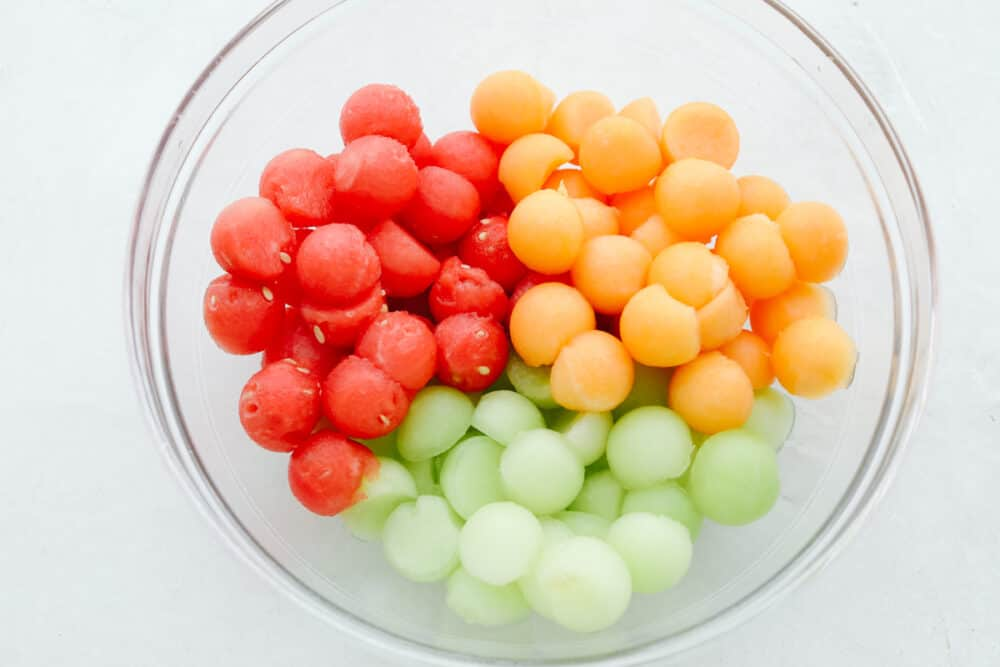 A bowl filled with fruit, all scooped as small pieces.