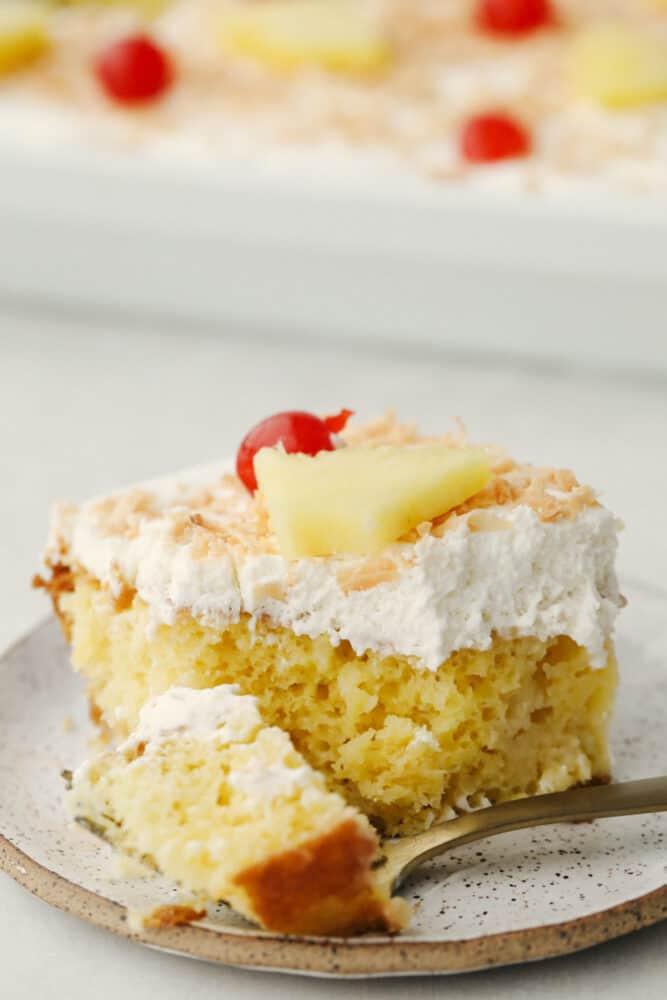 A slice of pina colada poke cake.