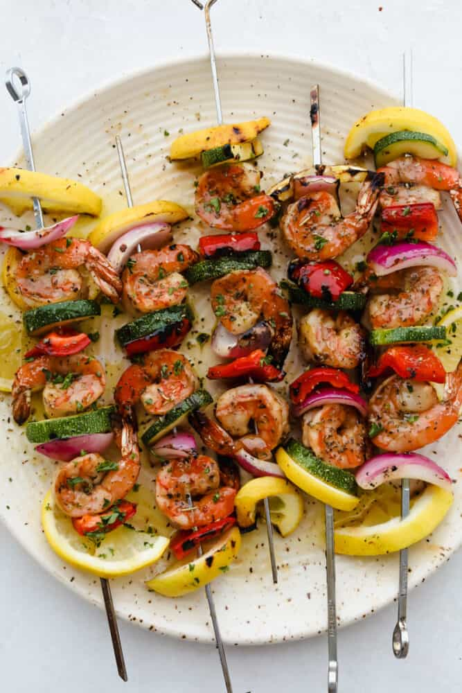Shrimp and vegetable skewers grilled and on a plate ready to eat.
