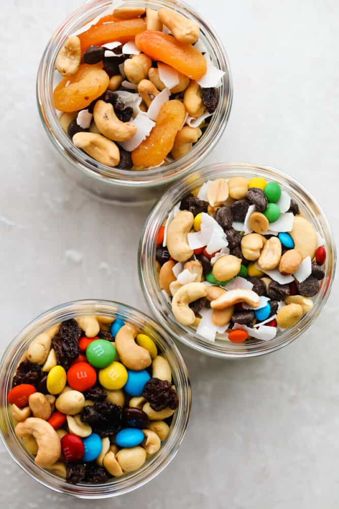 Glass jars filled with all three trail mixes.