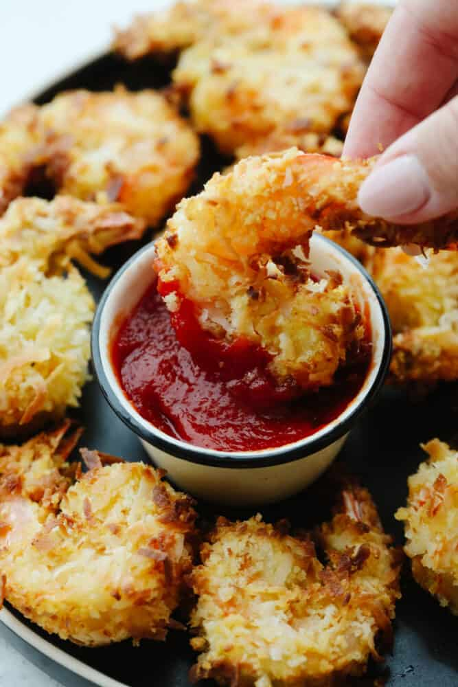 Air fried shrimp being dipped into sauce.