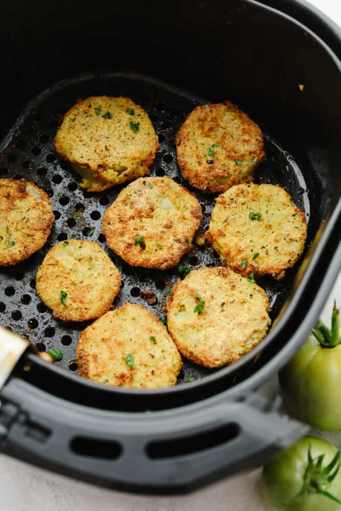 Green tomatoes frying in an air fryer.