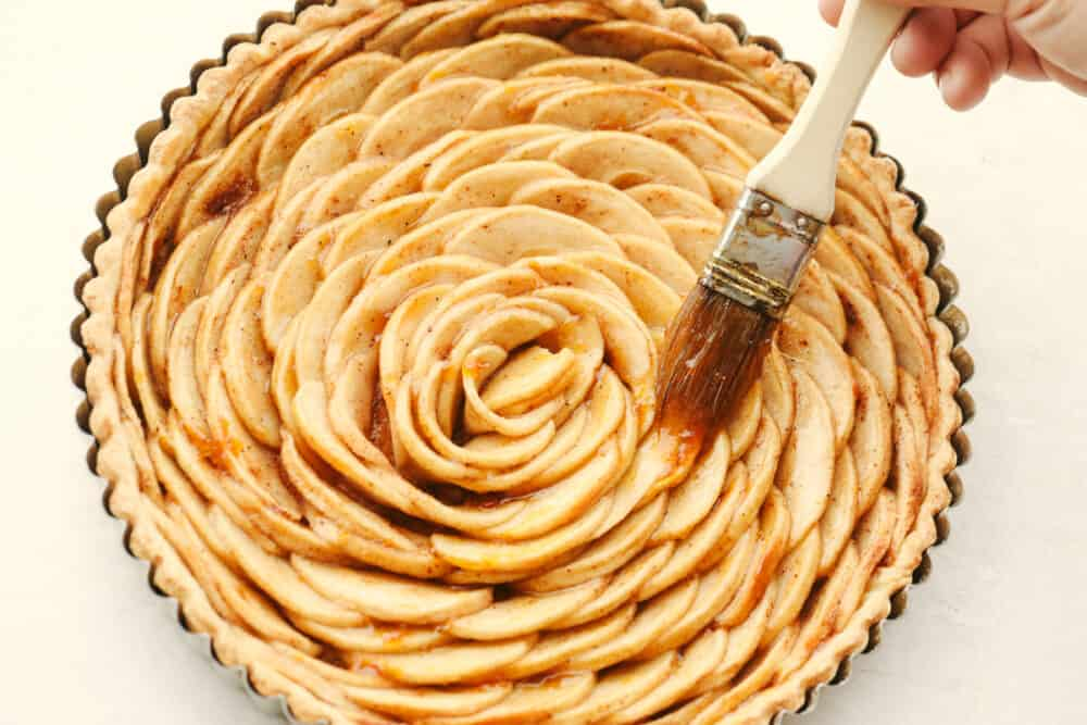 Brushing the top of the pastry with apricot preserves.