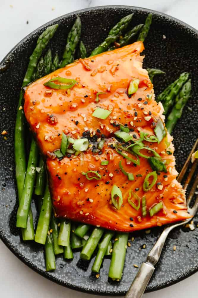 Asian glazed salmon served on top of asparagus.
