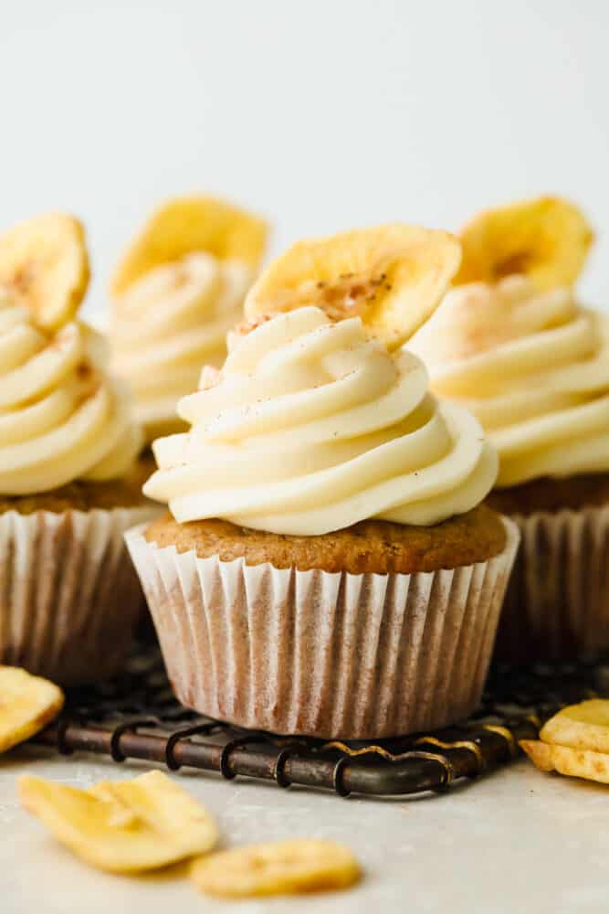 Banana cupcakes with cream cheese frosting topped with a single, dried banana.