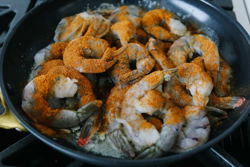 Uncooked shrimp sprinkled with seasoning.