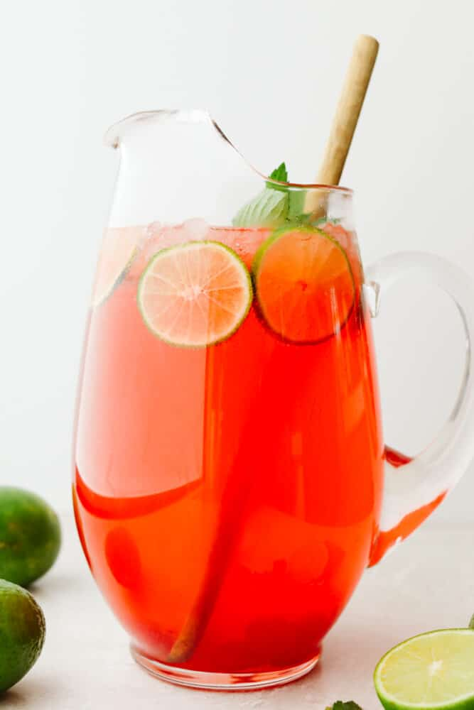 Cherry limeade in a pitcher with lime and mint garnish.