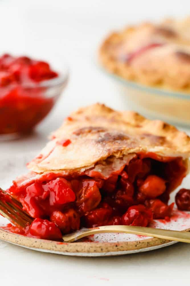 A slice of cherry pie on a plate with a fork.