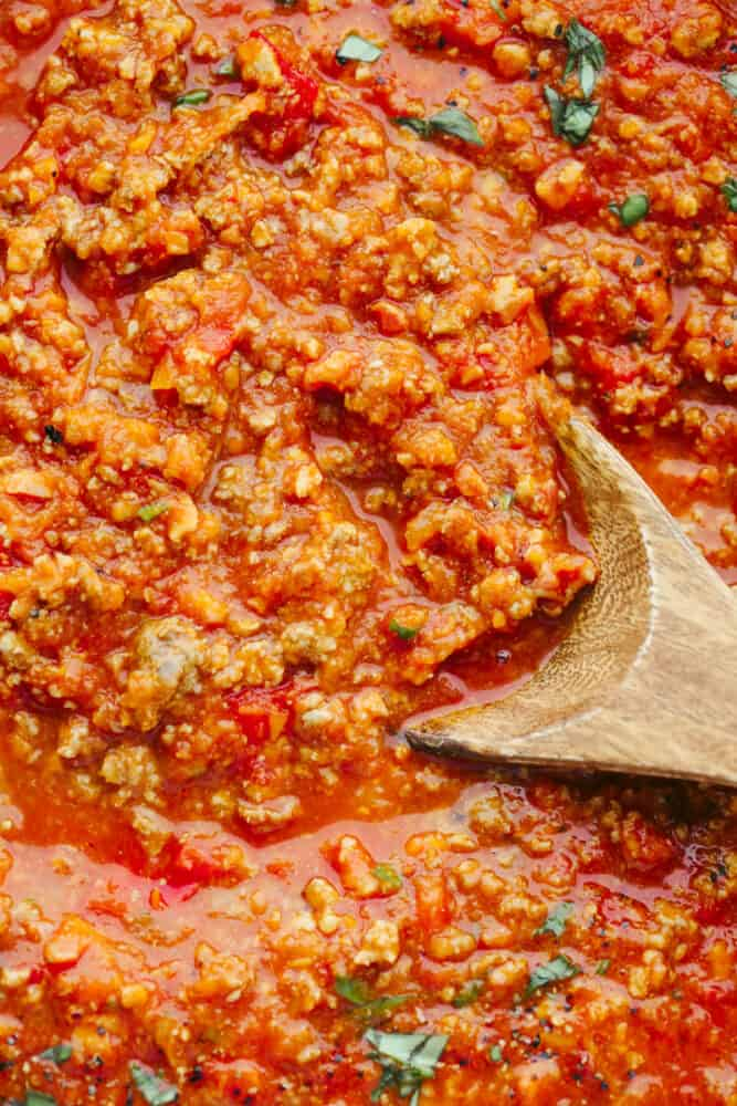 Zoomed in picture of the sauce with a wooden spoon in it.