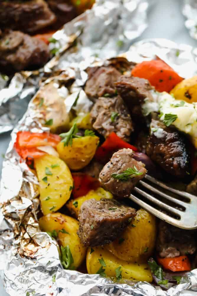 Steak foil packets opened with a fork in a steak.