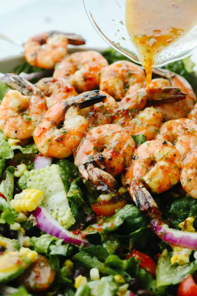 Pouring dressing over greens and grilled shrimp.