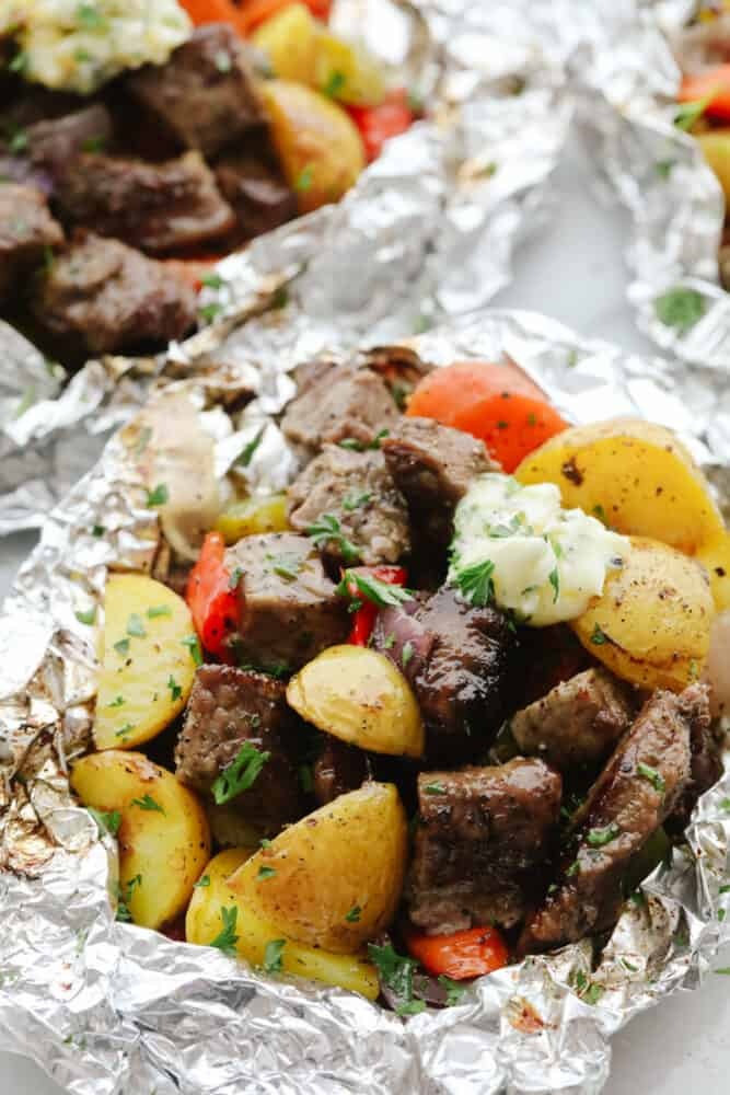 Close up of steak and vegetables in foil.
