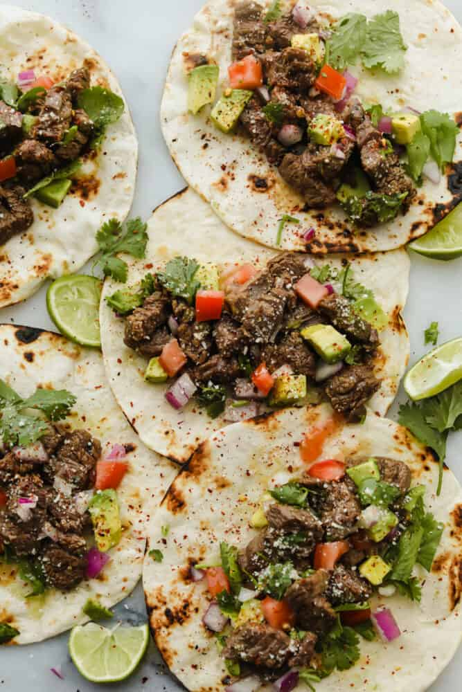 Tortillas being topped with steak and taco toppings.