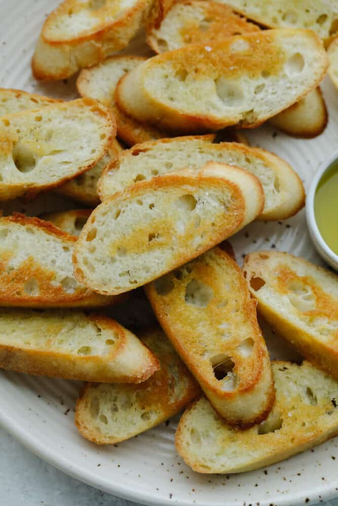 Closeup of crostini pieces on a white plate.