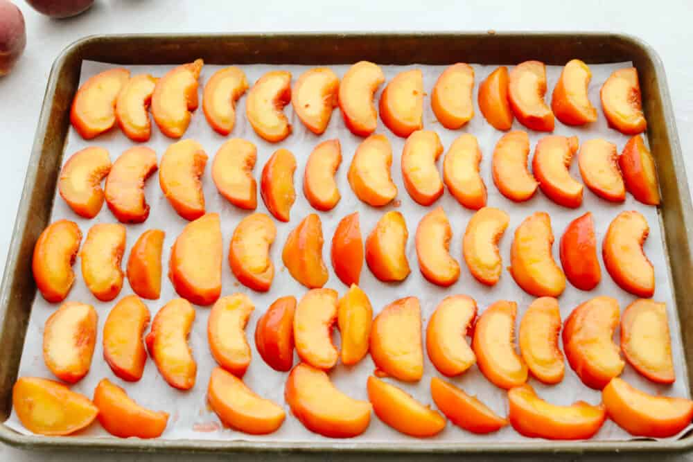 Peaches lined up on parchment paper on a baking sheet.