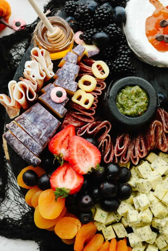 A charcuterie board with fruit being added.