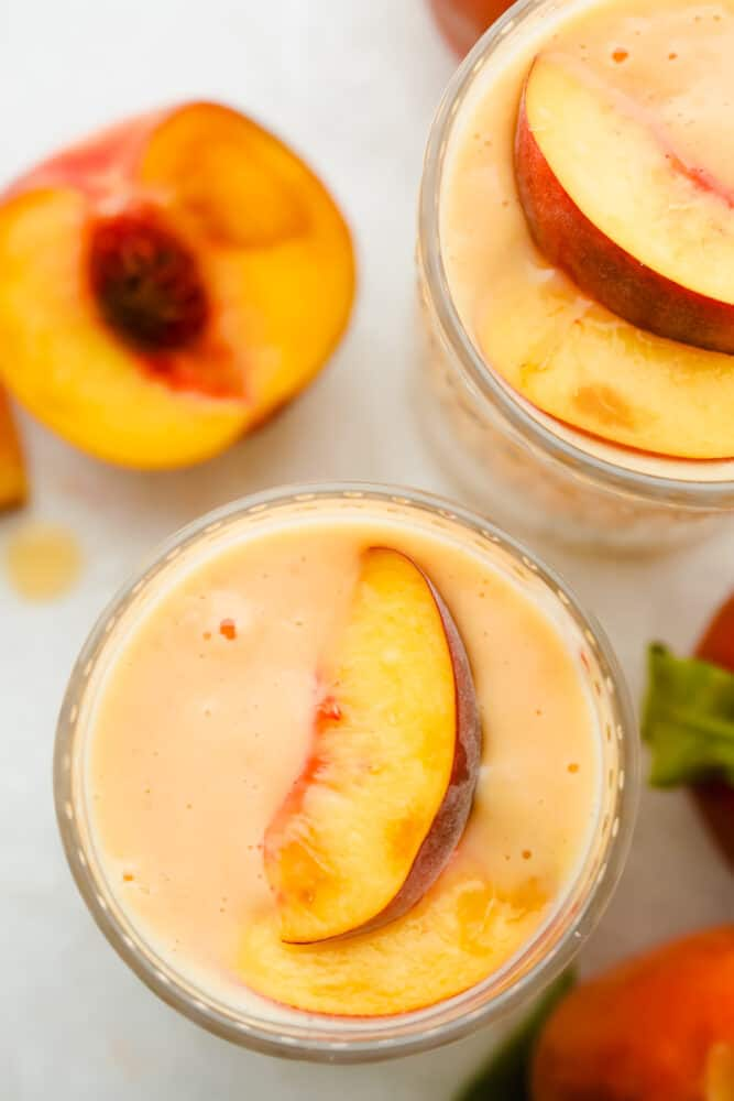 Topview of a peach smoothie with a peach garnishing the top.