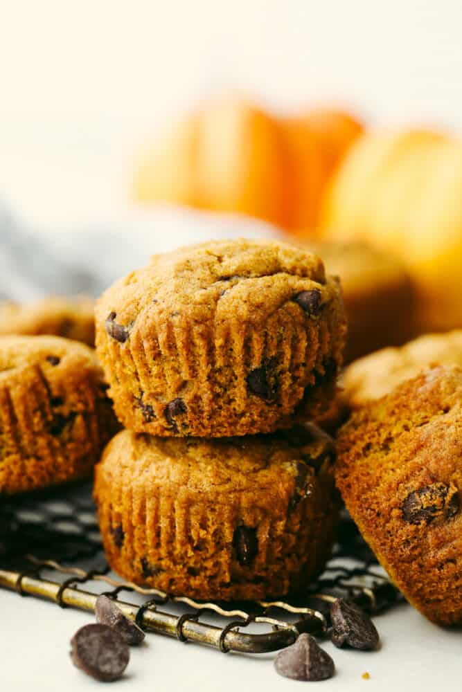 Pumpkin chocolate chip muffins stacked on top of each other.