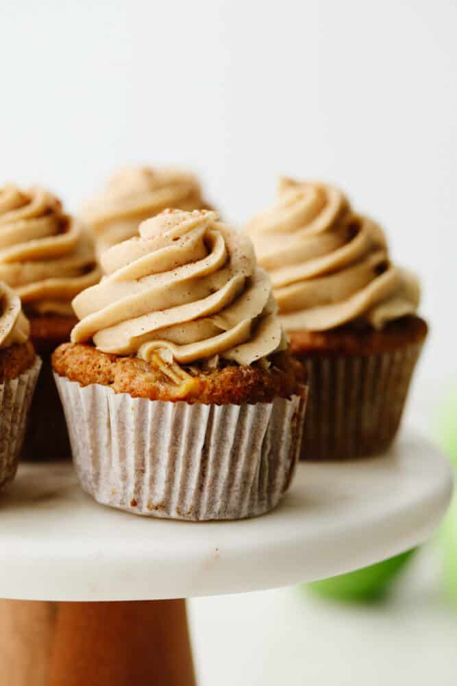 Close up of an apple pie cupcake on a cake stand.