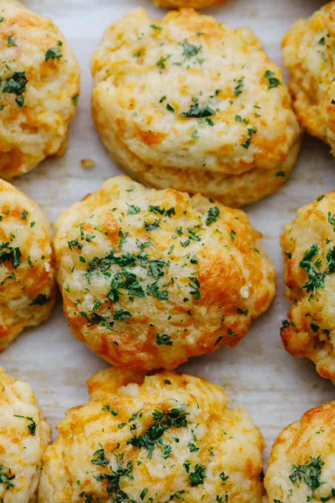 Closeup of cheddar biscuits on parchment paper.