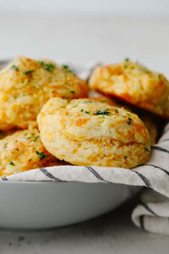 A stack of cheddar biscuits in a gray bowl.