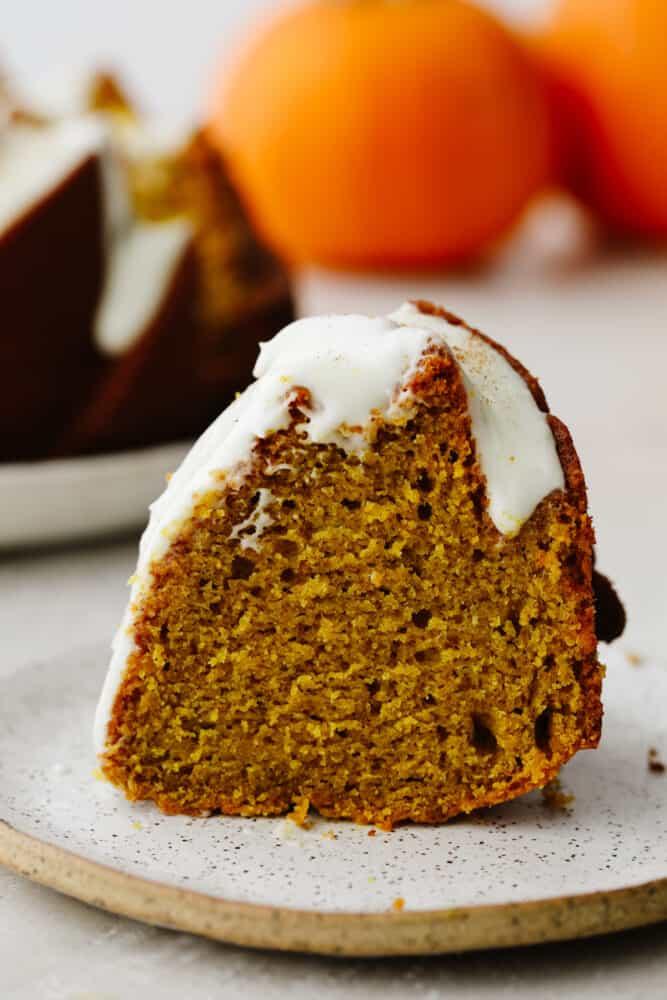 Slice of pumpkin bundt cake with frosting.