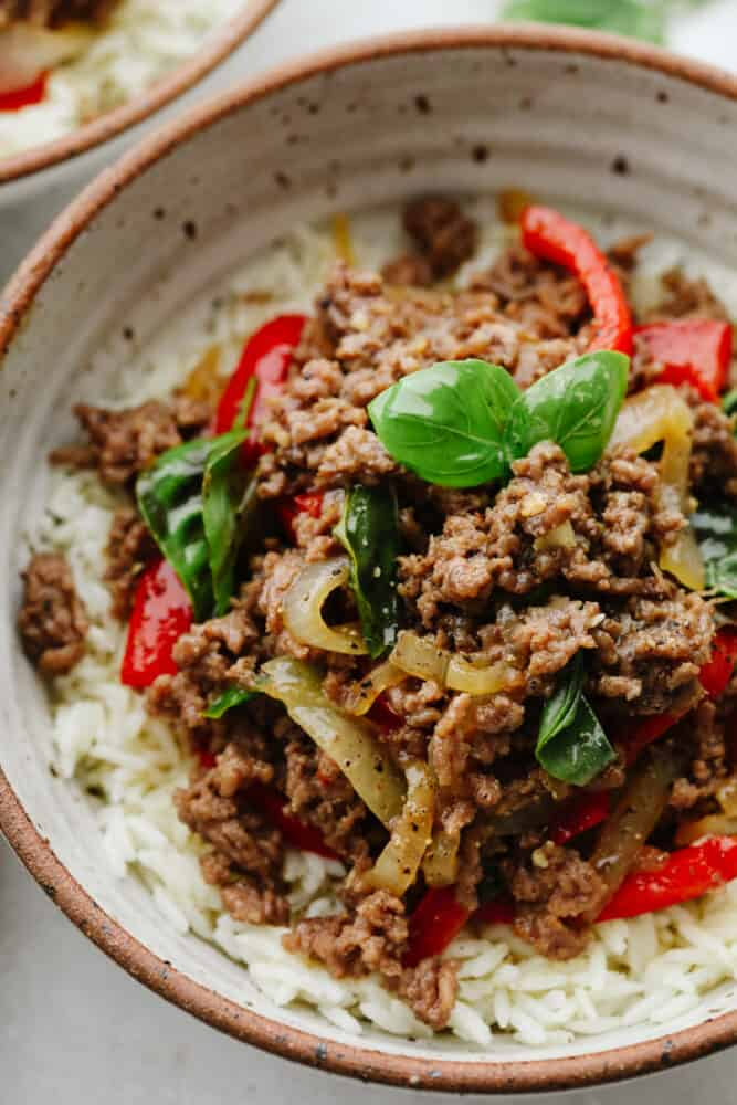 A close up of Thai basil beef on rice, in a bowl.